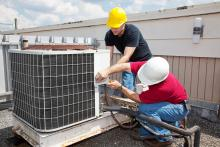 Technicians servicing an outdoor air conditioning unit