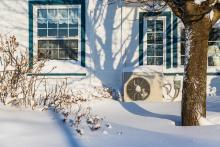 heat pump on exterior of house in winter snow