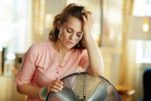 woman at home next to fan, house too hot in summer
