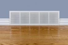 air vent in home with light blue walls and hardwood flooring