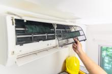 man cleaning air conditioner filter