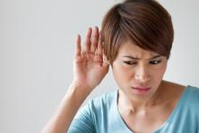woman listening for a noise in house