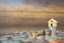tiny model house on stack of coins