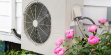 heat pump outside of home next to flowers