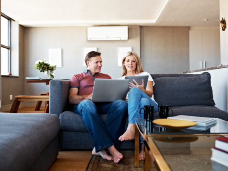 couple on couch below mitsubishi electric hvac system