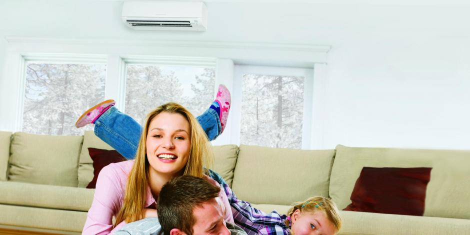 family playing on the ground in front of Mitsubishi Electric mini-split