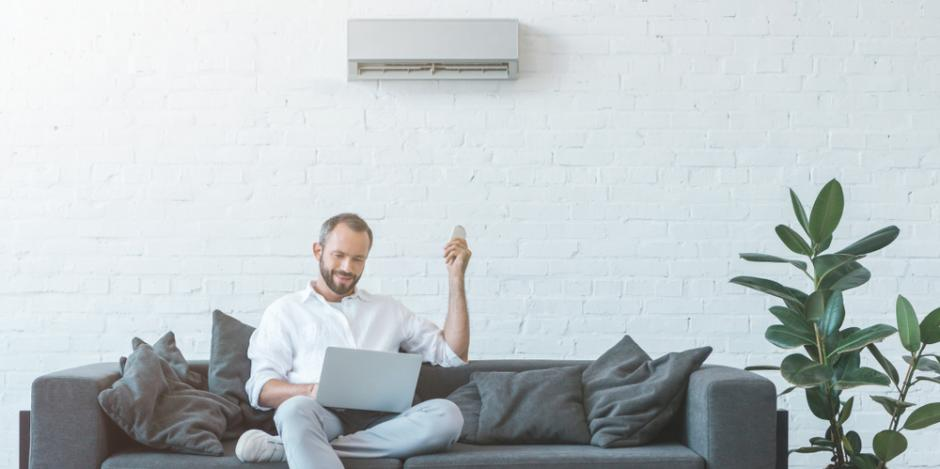 man on couch at home adjusting mini split on wall