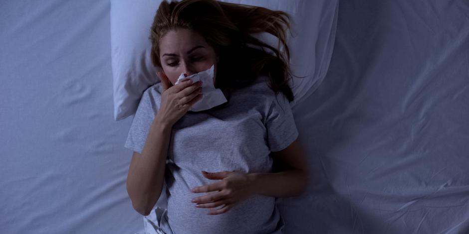 Pregnant woman blowing nose in bed