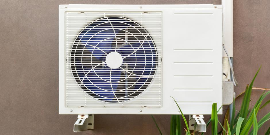 heat pump on exterior of home with greenery