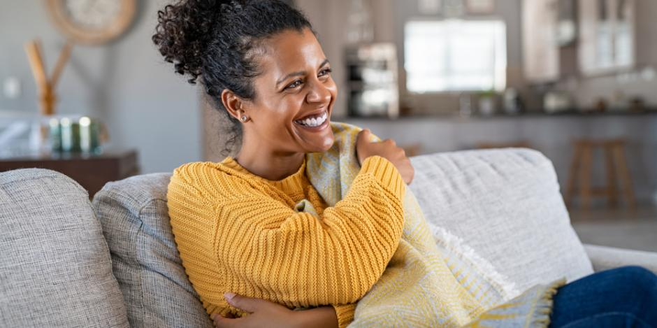 woman happy cozy at home on couch