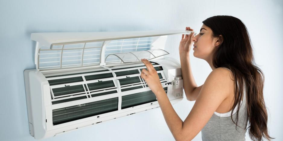 Woman checking mini split air filters in home