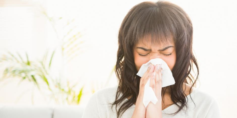 woman at home sneezing from indoor allergies