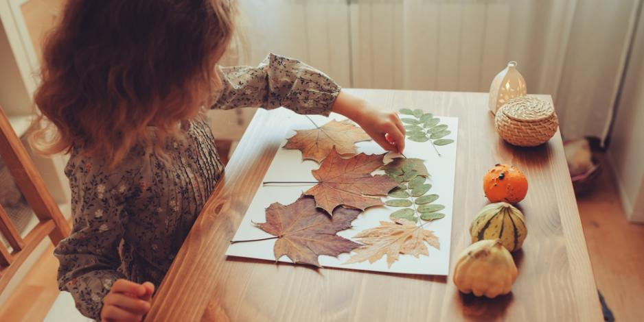 child playing with leaves and pumpkins at home