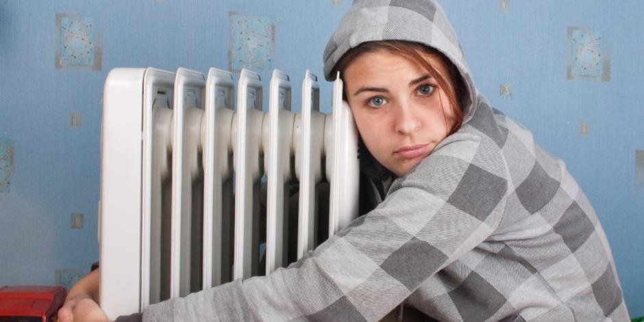 cold girl hugging heater